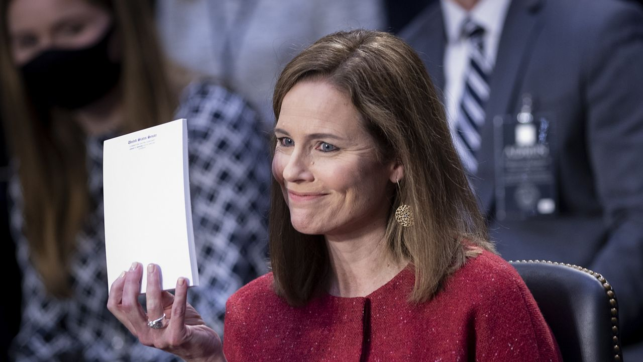 Amy Coney Barrett answers questions at confirmation hearing without notes, holds up blank notepad